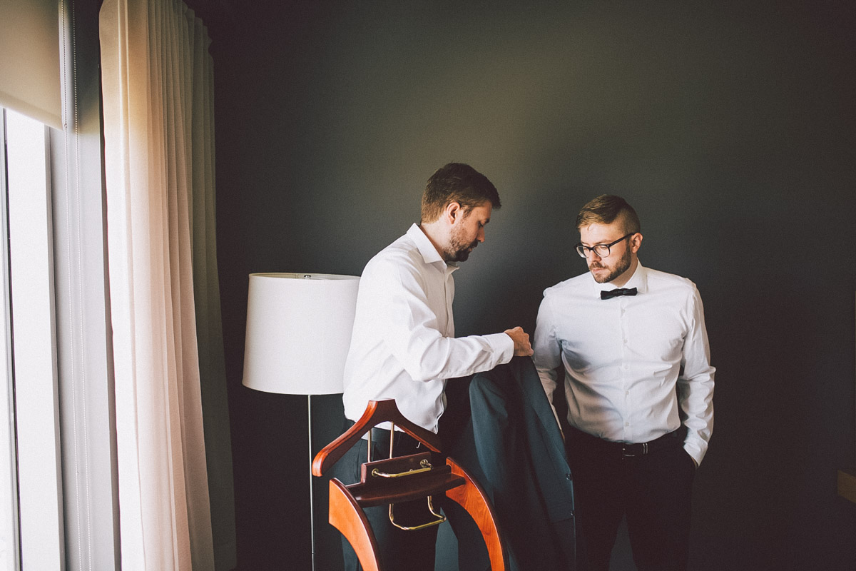 groom being helped with black tuxedo