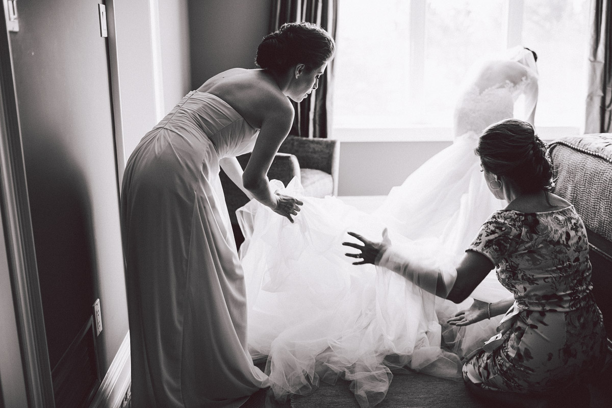 bridesmaids helping with wedding dress train