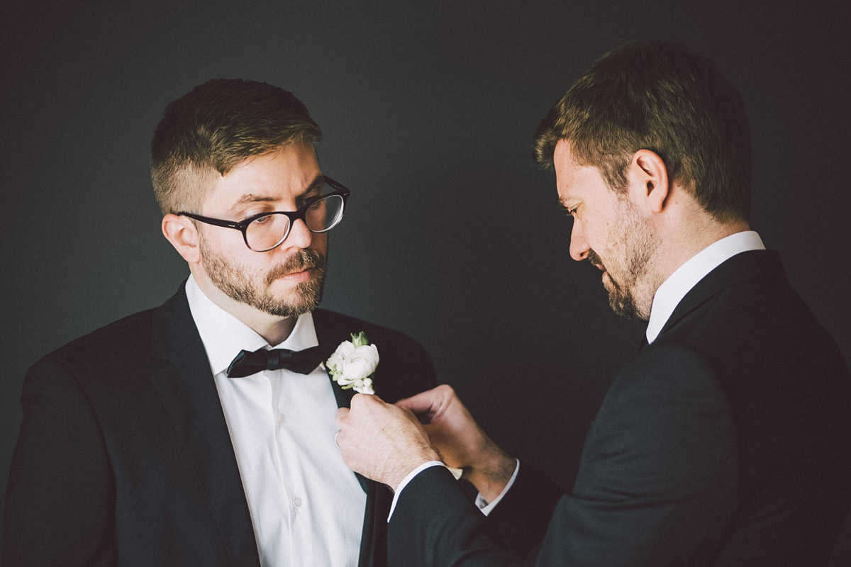 groom being helped with the flower