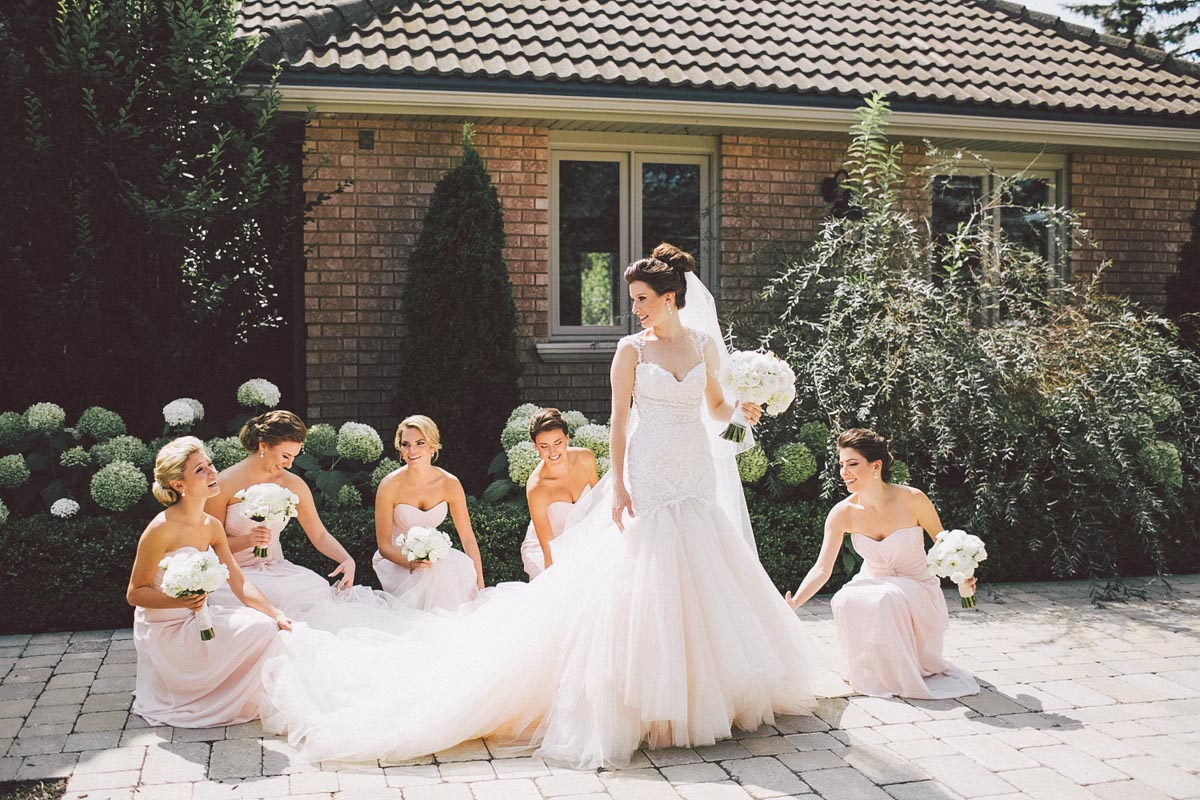 bridesmaids playing with brides dress
