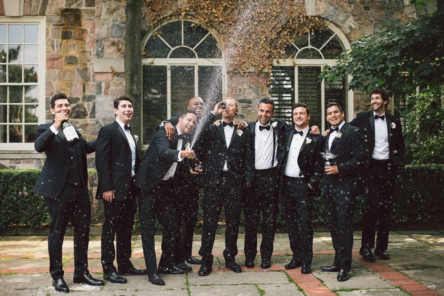 groomsmen opening up champagne