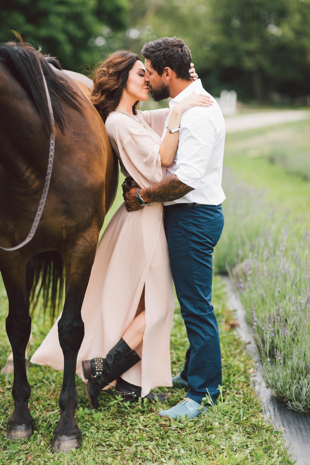 couple posing next to the horse