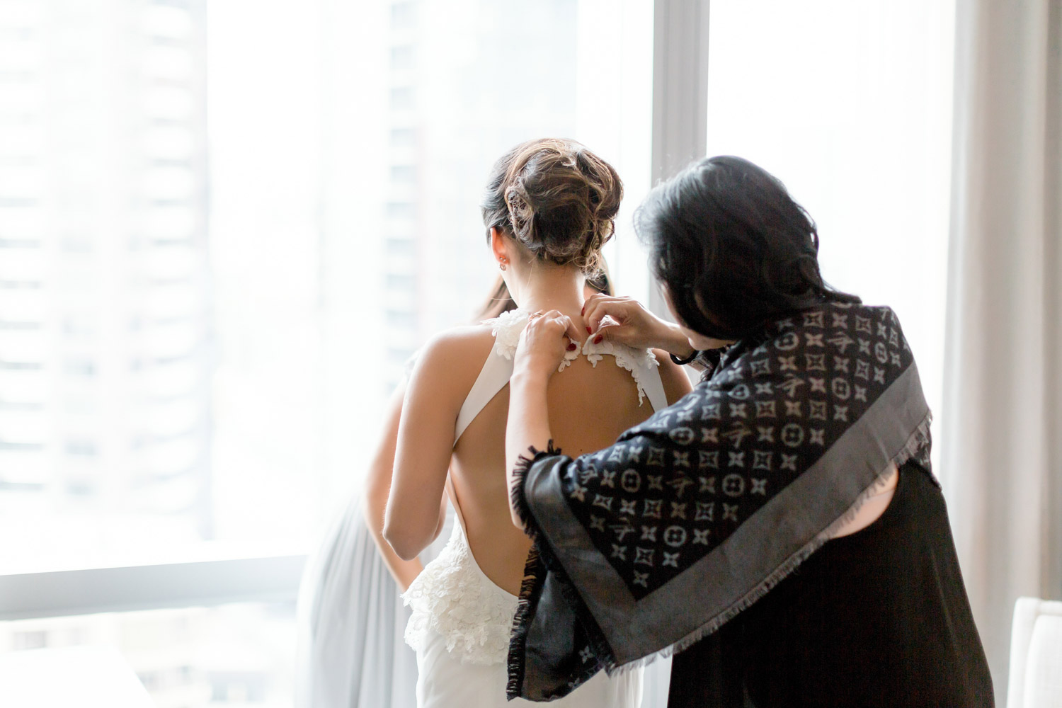 helping bride with the dress