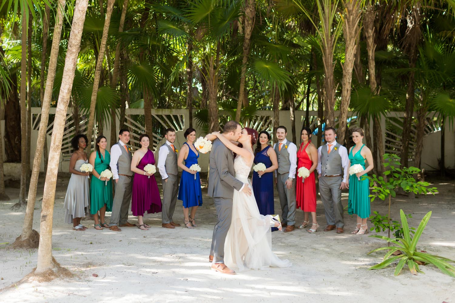 bride and groom kissing in front of bridal party