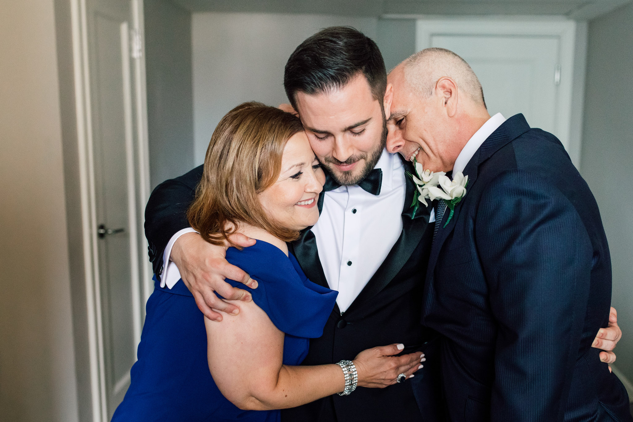 Groom and parents hug